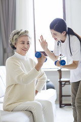 Senior woman exercising with dumbbell in nursing home