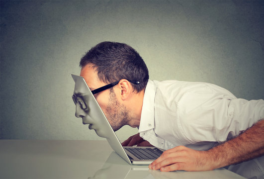 Business man in glasses passing his head through a laptop screen