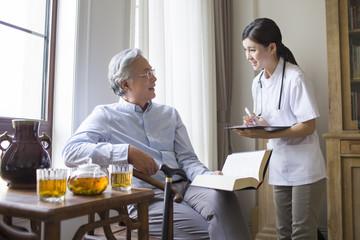 Nursing assistant talking with senior man