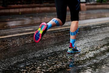 Wall Mural - woman running urban marathon in kinesiotape calf muscles