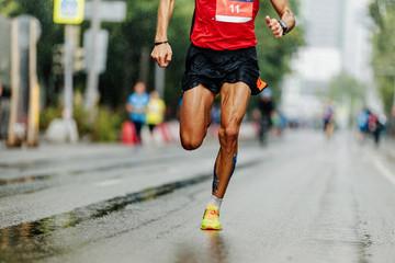 Wall Mural - leader athlete runner running city marathon in rain