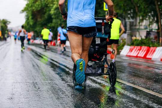 male athlete running city marathon with baby carriage