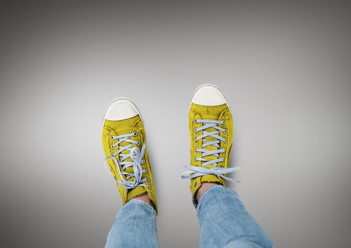 Yellow shoes on feet with grey background