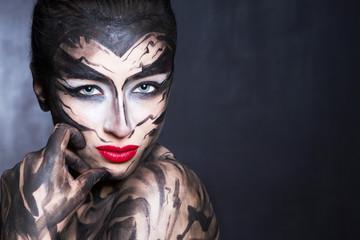 Разрисованная женщина черной краской с сконцентрированным взглядом.