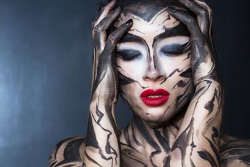 Женщина с разрисованным телом и лицом испытывает эмоцию стресса.