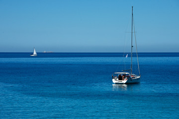 seascape with a sailing boat moored in a blue sea and an other sailing boat in the background with a blue sky