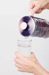 pouring of water from a jug in glass