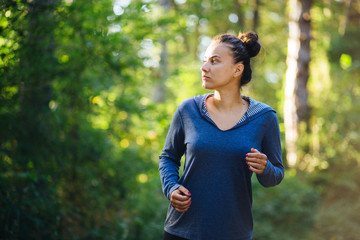 Young female model jogging in the woods