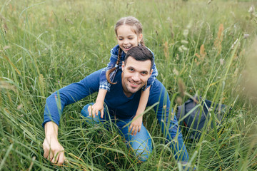 Playful attractive girl embracing her father who is sitting back to her, spending their free time together on green field. Handsome young man giving piggyback ride to his daughter in green grass