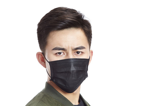 asian man wearing black mask looking at camera, isolated on white background.
