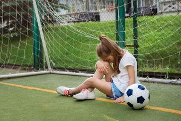 Little active girl wearing T-shirt, jean shorts and running shoes, hanging her head while being upset to miss goal in gates. Unhappy female kid goalkeeper playing football, crying because of defeat