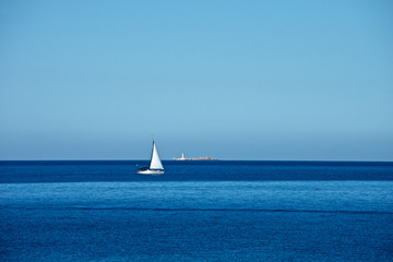 seascape with a white sailing boat sailing in the blue sea and in the background the sky and a lighthouse