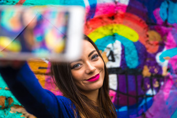 Hipster woman taking selfie photos in colorful abstract wall