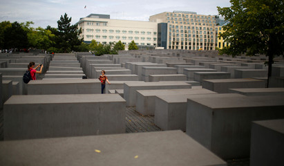 Tourists take pictures at the Holocaust Memorial in front of the U.S. Embassy in Berlin