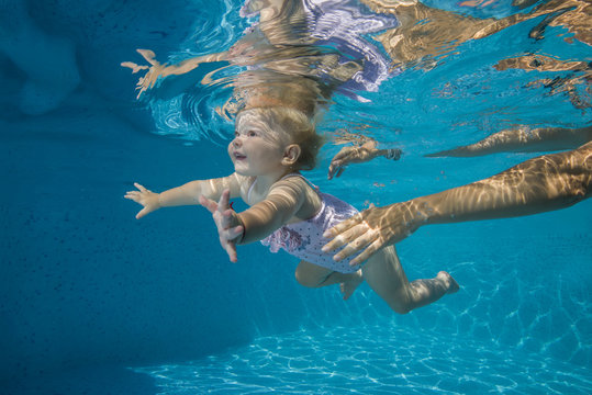 little child learns to swim underwater in the pool