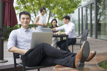 Young businessman using laptop outdoors