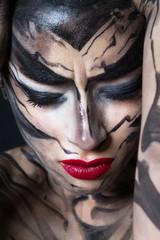 Разрисованная женщина с красными губами тихо плачет.