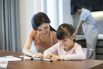Happy mother and daughter drawing pictures