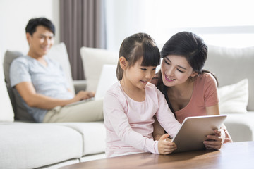 Happy young family using digital gadgets at home