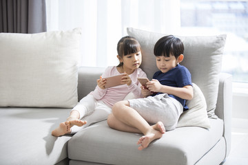 Happy boy and girl playing smart phones in sofa