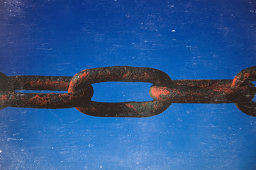 Old rusted chain on blue background. Strong connection between cells.