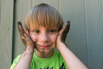 smiling boy with muddy face and hands closeup