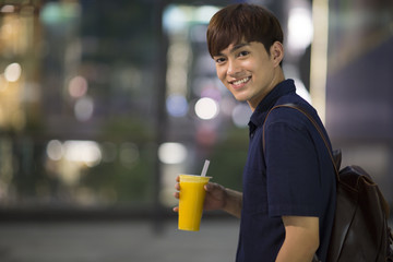 Happy young man holding a cup of juice