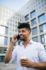 Young handsome Afro American man standing in front of huge modern business building smiling and talking on cell phone