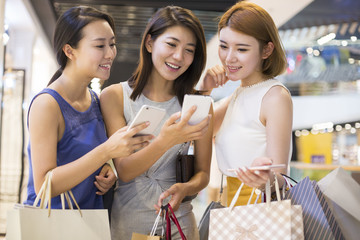 Young friends using smartphone while holding shopping bags
