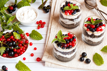 A sweet dessert of sponge cake with cream in a glass with fresh berries on wooden background