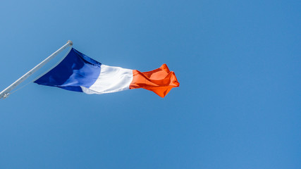French flag against a blue sky with copy space