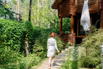 Beautiful redhead bride in silk dressing gown running barefoot to her wedding dress hanging on wooden house in the forest, free space. Wedding morning preparation in sunny summer day