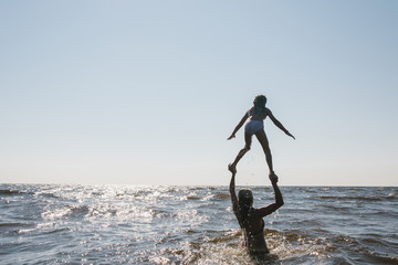 Mother carrying her daughter on hands in sea