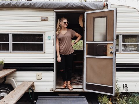 Stylish woman and vintage trailer
