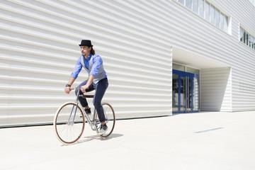 Fashionable man cycling in urban area