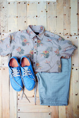 Men's clothes, sneakers and a shirt on a wooden background