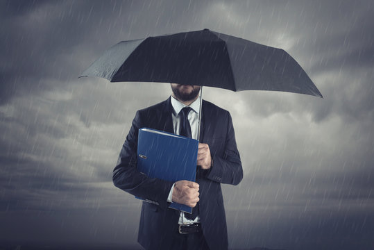 businessman below storm with umbrella