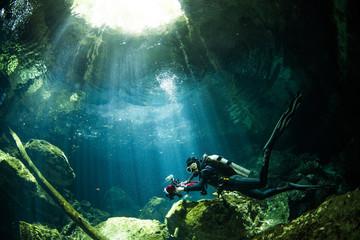 A scuba diver swimming in Mexico's Cenote Tajma Ha