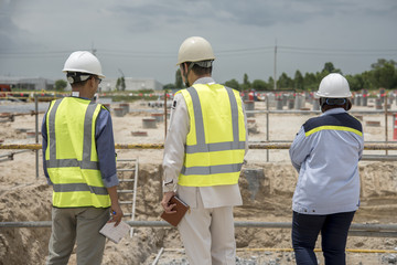 Group of workmen wearing protective helmets and vests walking among concrete walls of unfinished building showing development progress to foreman inspector on construction site