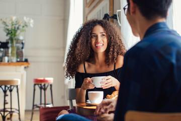 Happy trendy couple having breakfast in a coffee shop.