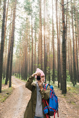 Girl in pink hat taking photo with camera in forest