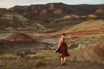 Young woman in red dress twirling around in the desert