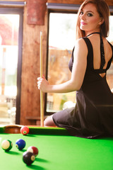 Young woman posing having fun with billiard.