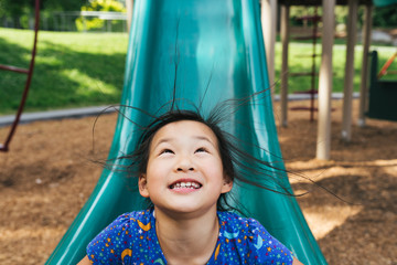 Young Asian American girl on playground slide with hair standing up from static electricity