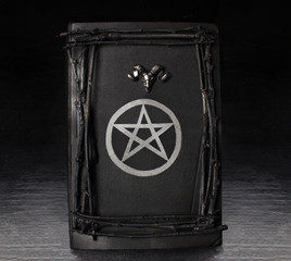 Black magic book with pentagram symbol and ram's head on