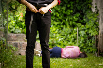 Close up of a man adjusting his pants after a sexual abuse, with woman laying in the ground behind the rapist. Rape and Sexual abuse concept