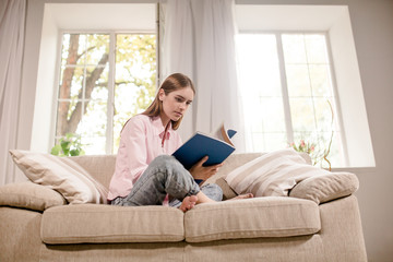Girl at home sitting on couch reading magazine. View of young female in comfortable living room, holding magazine in hands, sitting on couch.