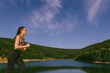 Fitness enthusiast running by a small beautiful lake