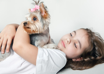 A girl with a dog looking to the side lying on white background