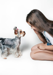 A girl with a dog looking at each other on white background